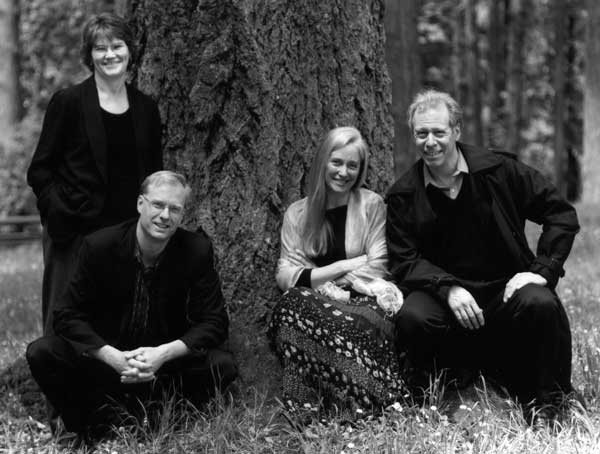 A photo of the members of Oregon String Quartet, outside under a large tree